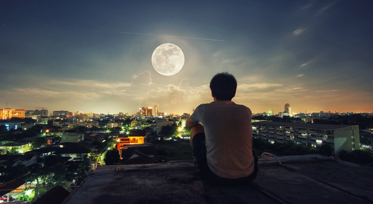 Man pictured from the back, sitting on a roof, looking at a full moon.