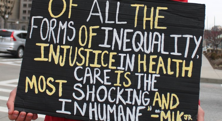 "A protester holds a sign with a quote that reads: ""Pf all the forms of inequality injustice in health care is the most shocking and inhumane."""