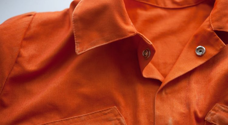 Up close shot of an orange prison jumpsuit
