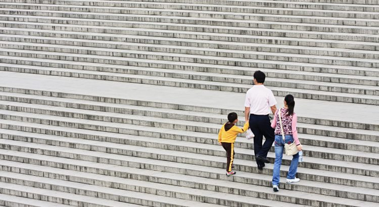 A family consisting of two adults and one child walk stairs with their backs to the camera.