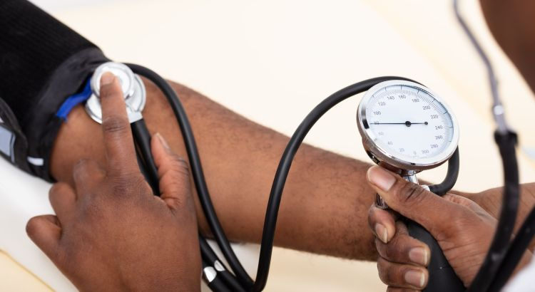 Close-up Of Doctor's Hand Measuring Blood Pressure Of Male Patient.