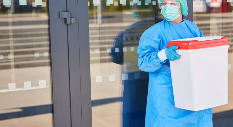 Doctor or surgeon with organ transport after organ donation for surgery in front of the clinic in protective clothing.