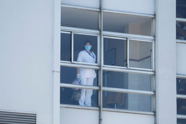 woman in PPE standing at window.