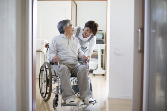 Woman helping man in wheelchair at home.