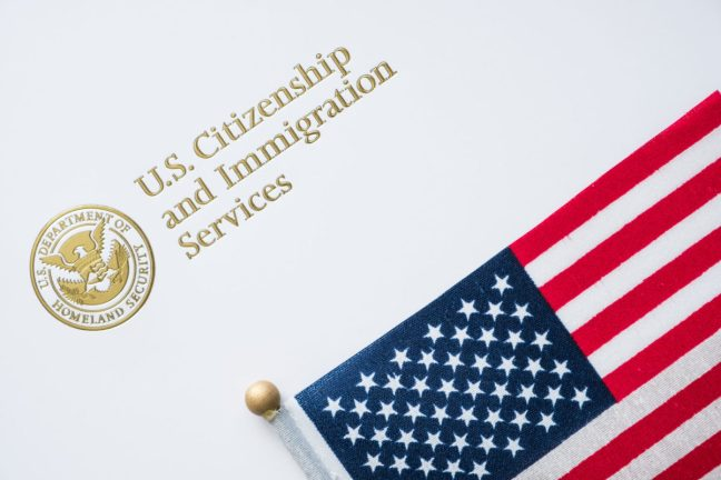 Envelope from U.S. Citizenship and Immigration Services with the American flag on top/U.S. immigration concept.