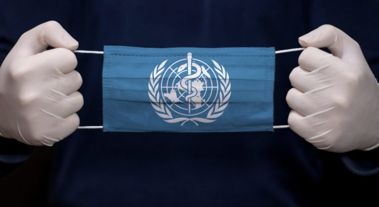 Gloved hands hold medical face mask with WHO (World Health Organization) flag.
