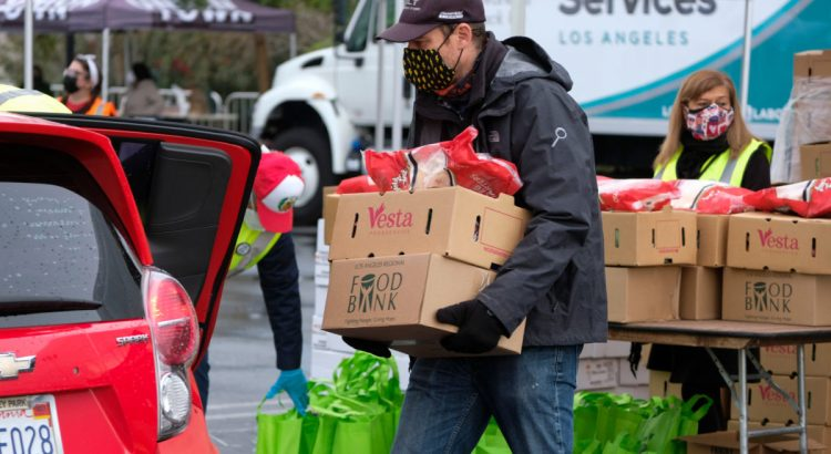 A volunteer loads food into the trunk of a vehicle during a drive thru food distribution by the Los Angeles Regional Food Bank at Exposition Park on Saturday, Jan. 23, 2021, in Los Angeles.