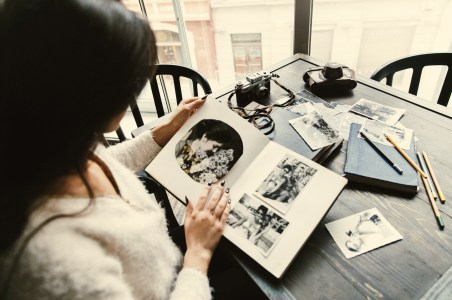 woman looking at old photo album