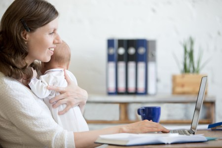 young woman holding a baby while on a computer