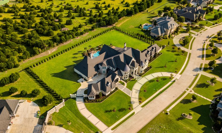 bird's eye view of a mansion on a green property with a pool.