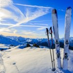 Ski in winter season, mountains and ski touring equipment on the top at sunrise
