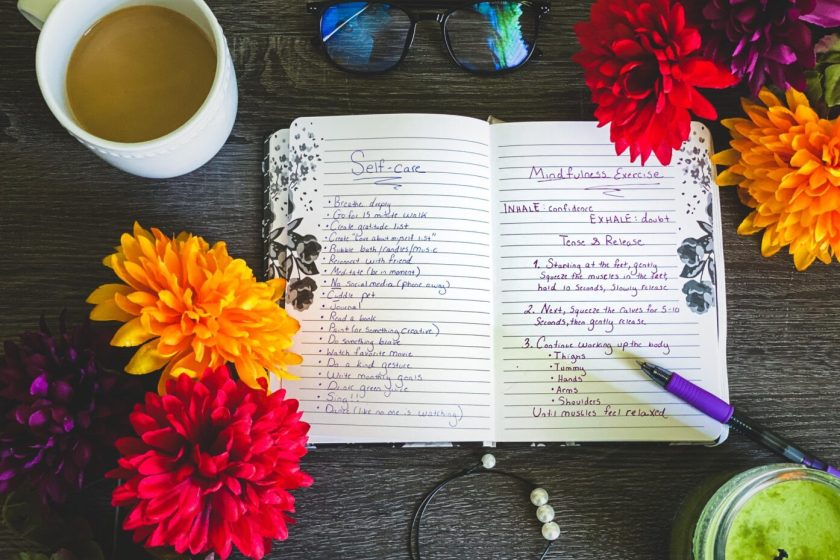 A flat lay photo of a journal with self care and mindfulness techniques