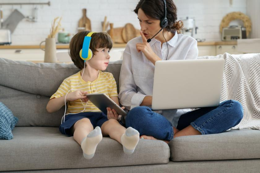 Nervous mother sitting on couch at home during lockdown, work on laptop, child distracts from work