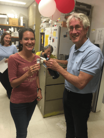"""Propel(x) expert and PhD candidate Emma Chory celebrates her acceptance into Science with co-writer Professor Professor Gerald """"Jerry"""" Crabtree by drinking champagne from a 50mL vial."""