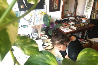 Aviva Reed working at desk with plant leaves in foreground