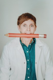 Woman with oversized pencil held in mouth.
