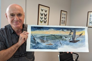 Man holding painting of birds over stormy sea