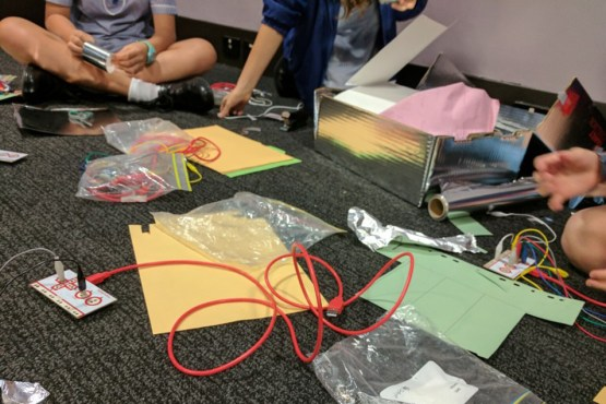School children doing a coding activity the uses wires, alfoil and other craft supplies