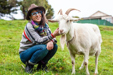 Illustrator Brenna Quinlan crouches in a green field smiling to camera, patting a white goat that stands next to her.