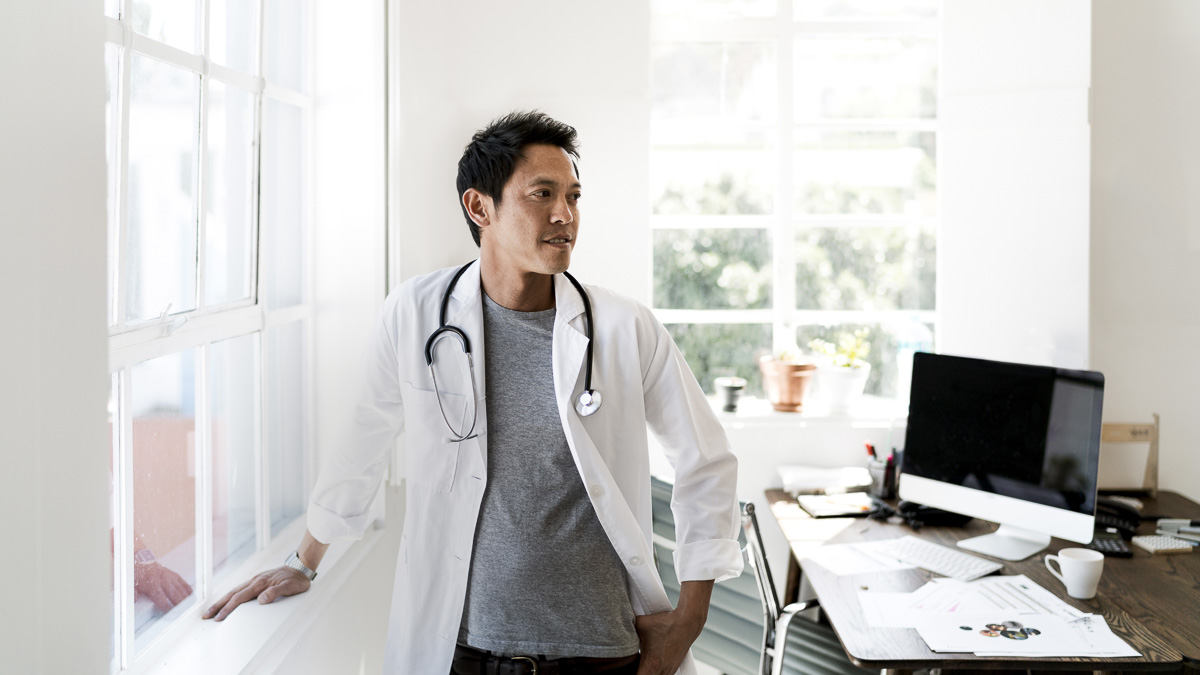 Thoughtful doctor standing by window in office