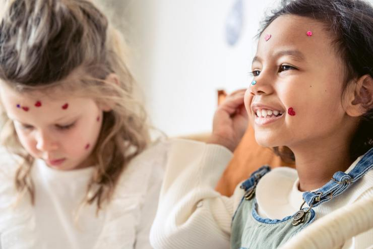 Two young girls play pretend with stickers on their face