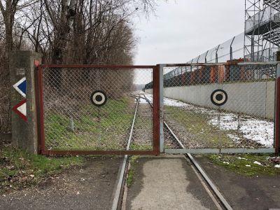Geschlossene Gittertore und ein Eisenbahnstrang
