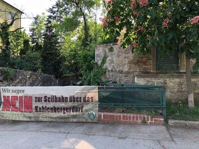 """Transparent """"Nein zur Seilbahn über das Kahlenbergerdorf"""" auf einem Gitter beim Waldbach im Kahlenbergerdorf"""