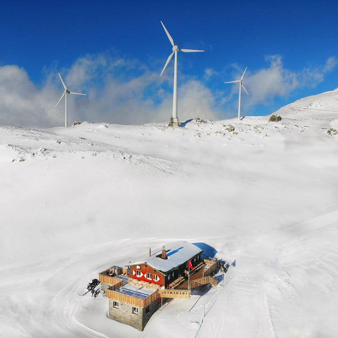 ski lodge with 3 large wind turbines behind it, surrounded by snow and blue skies