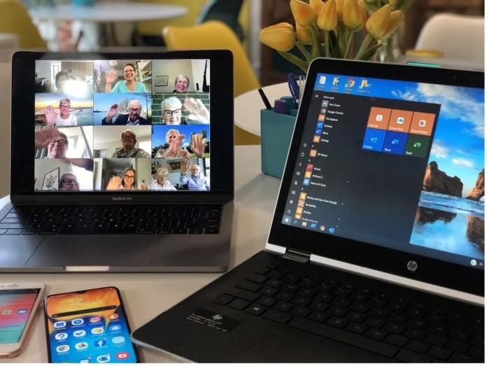 Zwei Laptops stehen auf einem Tisch, auf einem Laptop sieht man viele Personen in einem Video-Chat