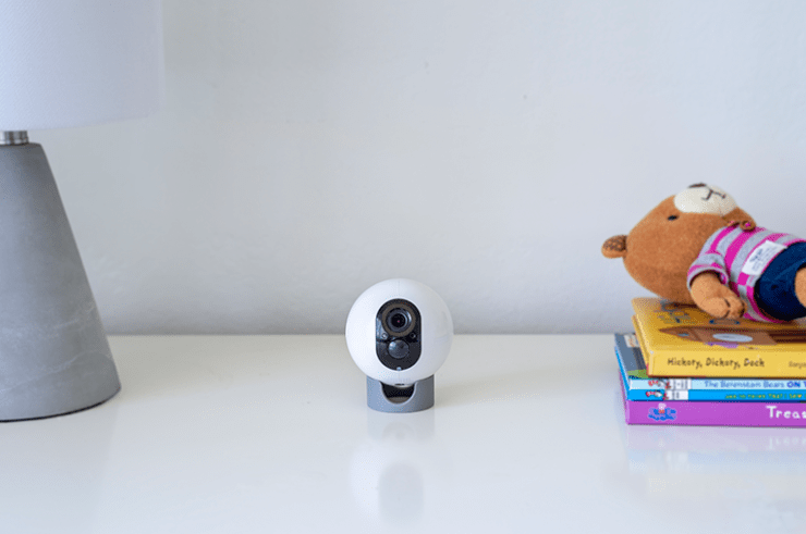 VAVA Home Cam Positioned On A Desk Next To A Lamp, Books, and a Teddy Bear
