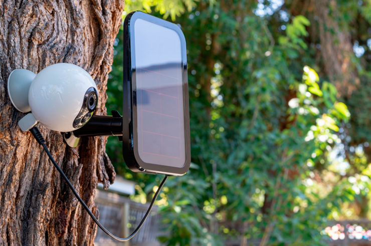 VAVA's Home Cam with a RAVPower Solar Charger stationed on a tree in a green garden