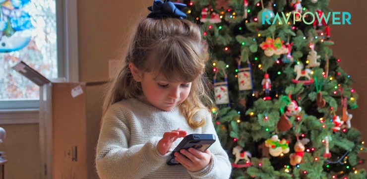 Little girl holding a portable device standing next to a Christmas tree
