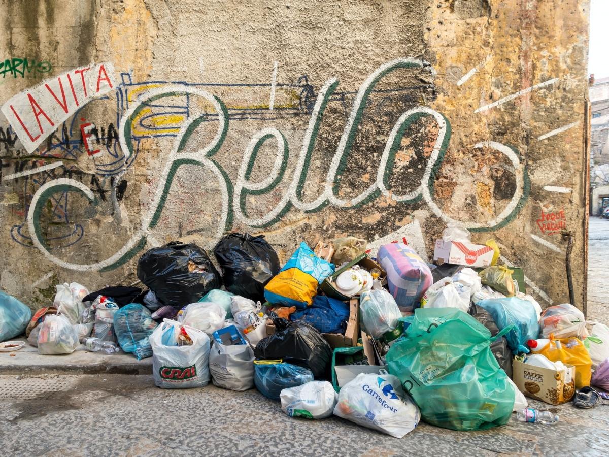 garbage bags in front of a graffitoed wall
