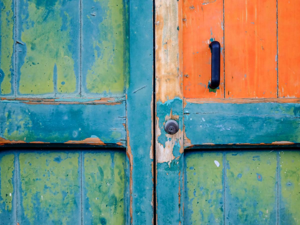 Old door with peeling paint in several colors