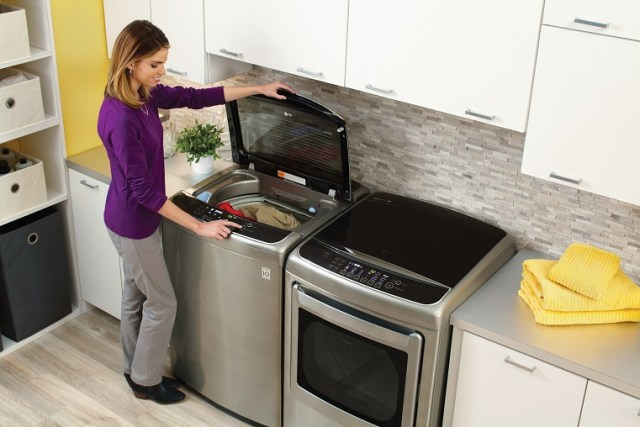 Woman uses washer and dryer set, washing machines has a pre wash compartment sink