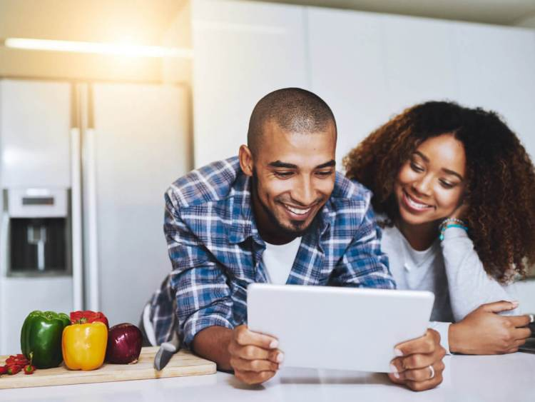 Couple in kitchen looking at cooking recipes on tablet