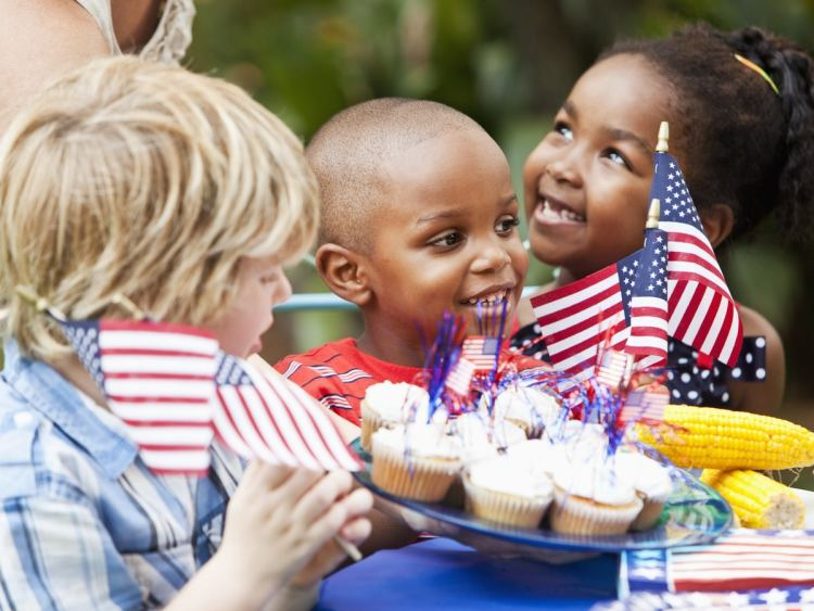 Three kids sharing cupcakes and corn decorated with patriotic streamers