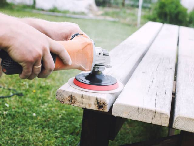 Using circular sander on wooden bench