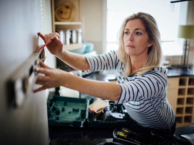 Woman using a pencil and leveler to install shelving at home