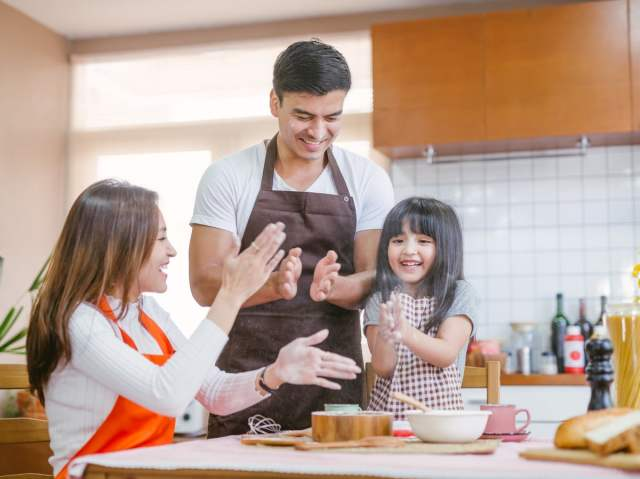 Parents and daughter dust flour off hands