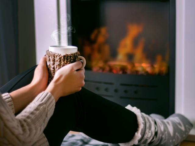 Woman sitting by a fireplace with a cup of coffee