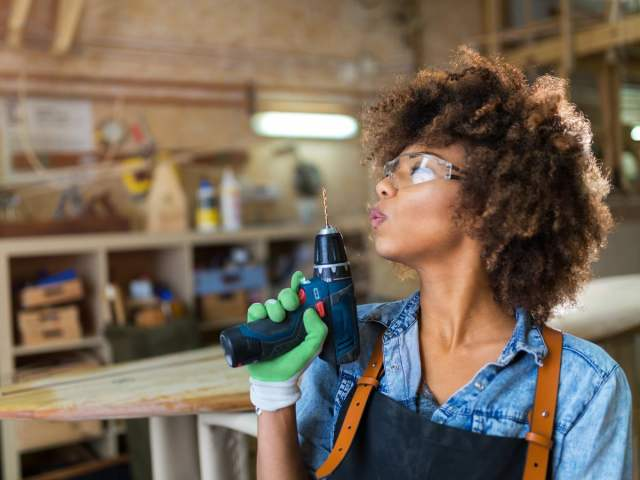 Woman holding up power drill