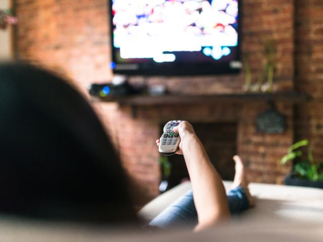 Woman pointing a remote at a TV