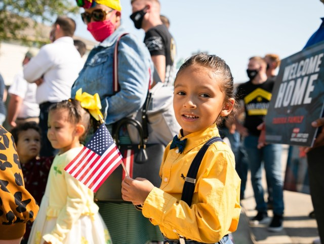 Child waves American flag welcoming military family to new home