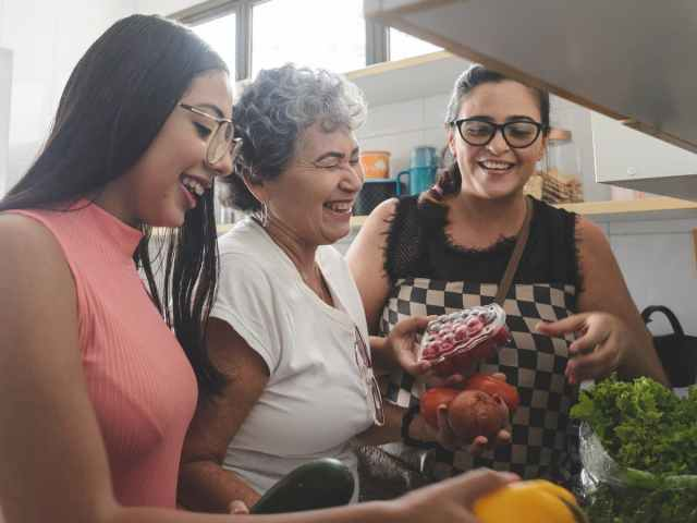 Three happy and smiling women in kitchen holding fresh produce
