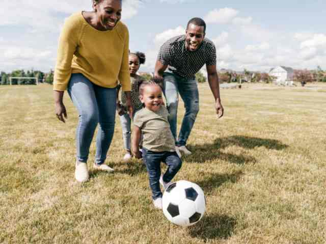 Family of four playing soccer in a sports field