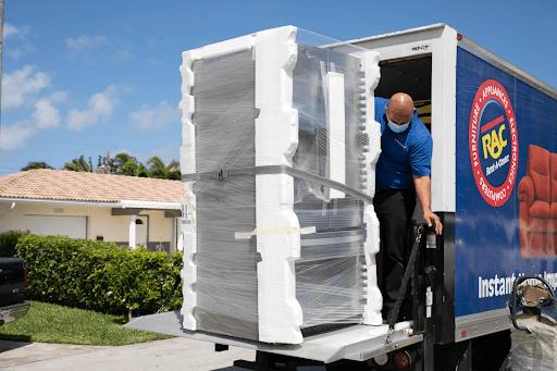 Man Unloading Appliance from Rent-A-Center Truck