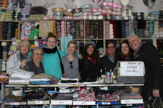 group of people smiling in a store selling yarn and fabric