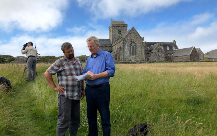 rick steves looking at a script and discussing it with his producer simon griffith while standing in a field in front of a castle