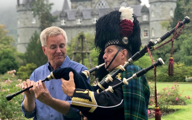 rick steves with a scottish piper